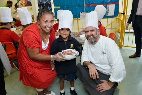 Vivianne Freeman from Barnardos with Uday Huja making meat balls with children at Yurungai Learning Centre.