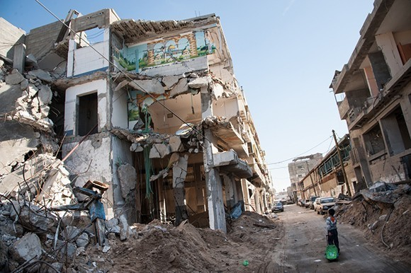 Child walks past bombed building in Gaza