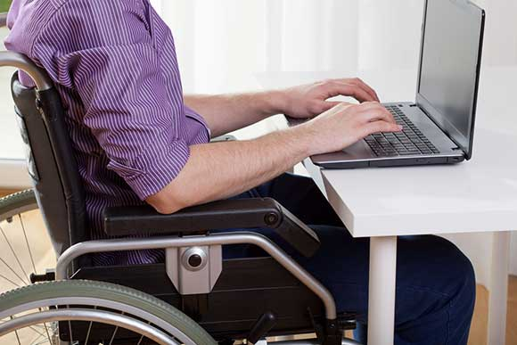 Wheelchair user on laptop
