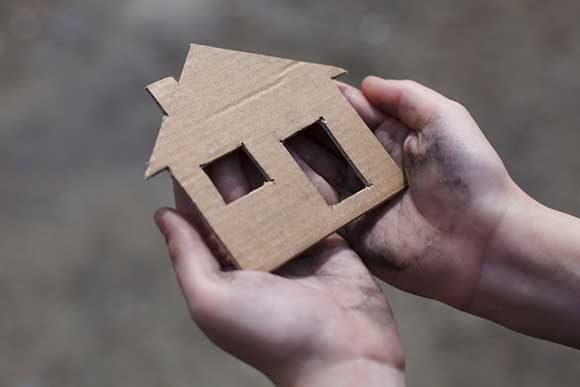 Homeless person holding cardboard house