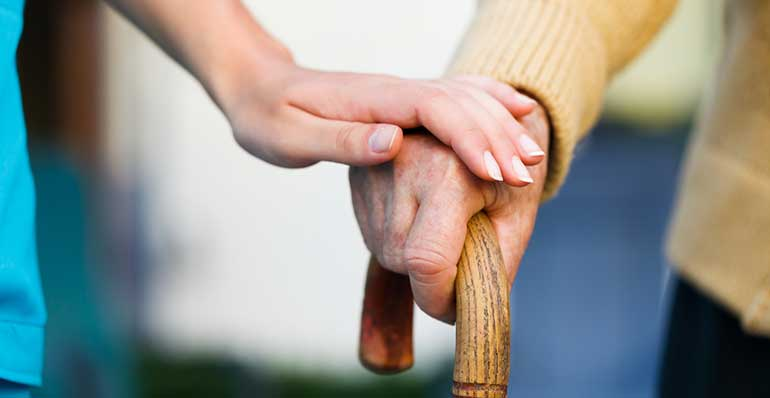 Aged care worker with patient hands on cane