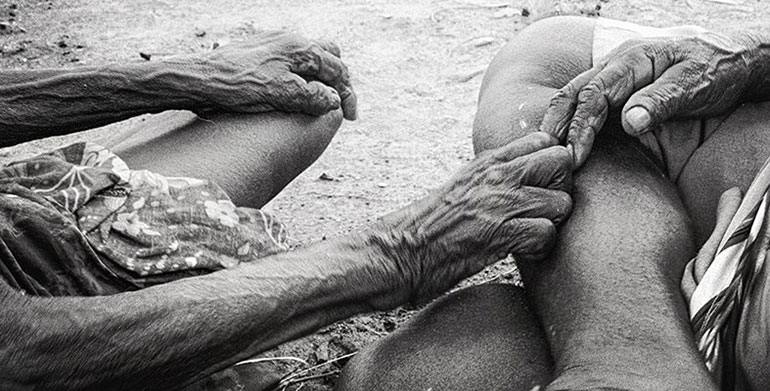 Indigenous people holding hands