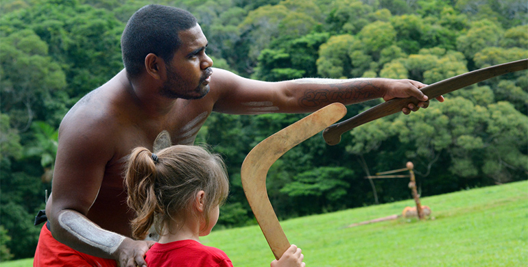 Aboriginal man teaches child in traditional ways