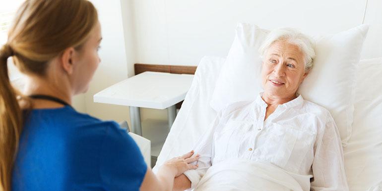 Nurse at the bedside of elderly lady