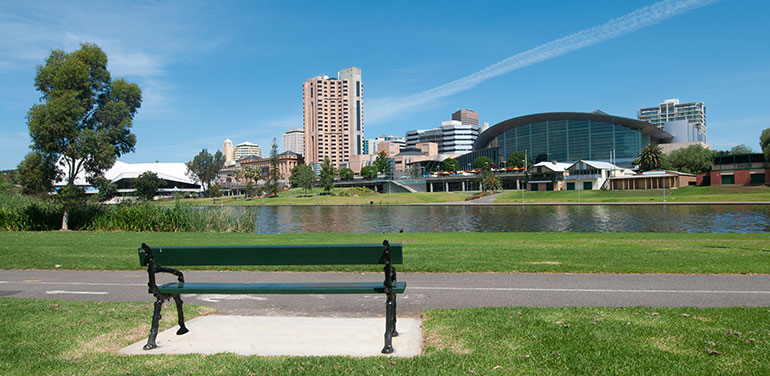 Empty park bench with Adelaide skyline in the background