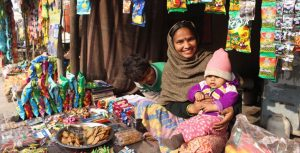 Female entrepreneur sitting in her stall with her children