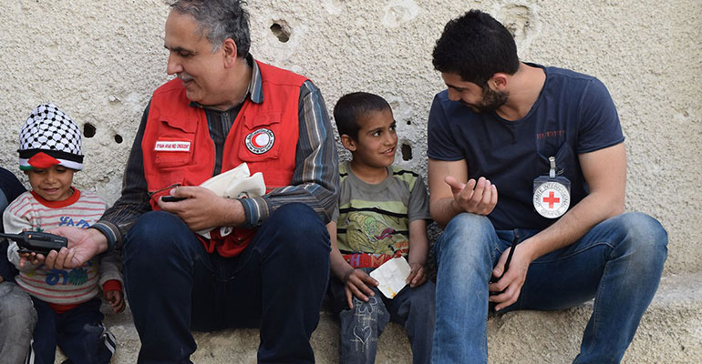 Red Cross workers speak with children in Syria