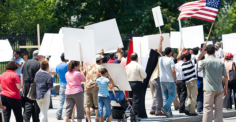 Protesters marching in the US with signs and flags