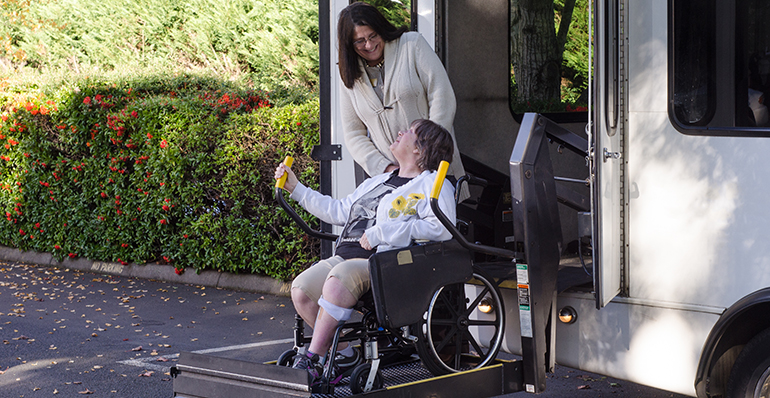 A woman in a wheelchair is helped off a van using a chair lift.
