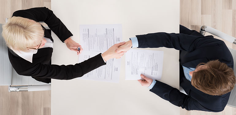 Overhead shot of two people shaking hands at job interview