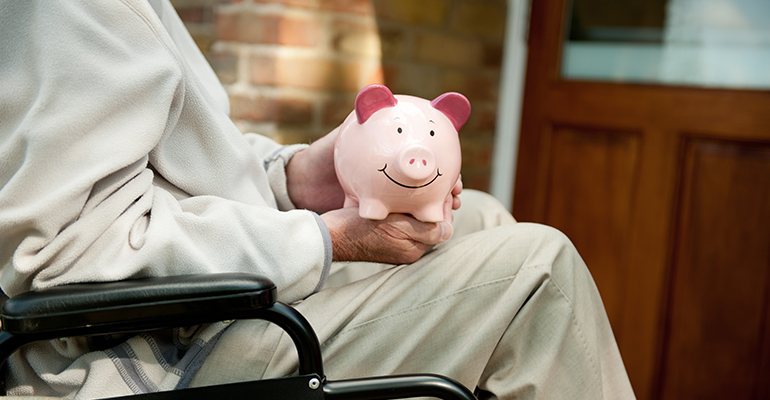 person with disability in wheelchair with piggybank