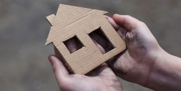 cardboard house in hands