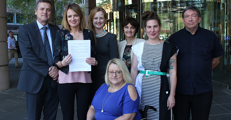 7 disability advocates in a group photo, smiling at the camera. The advocates are outside on a Melbourne street.