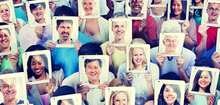 Lots of diverse people holding ipads with faces on the screen in place of their faces.