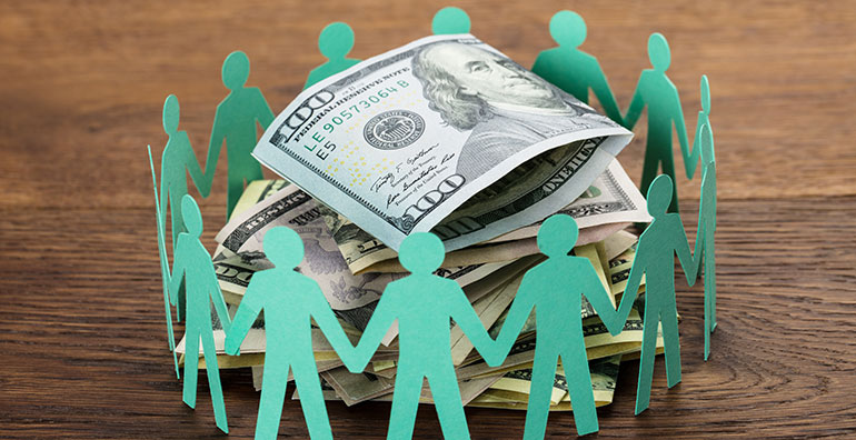 paper cut out of people surrounding money