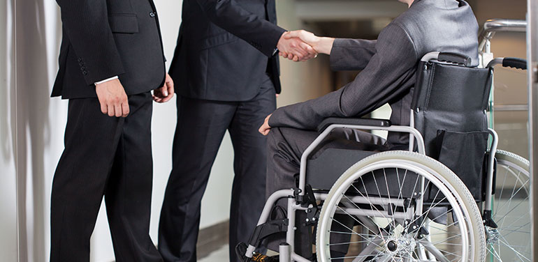 Man in wheelchair shaking hands with men in suits