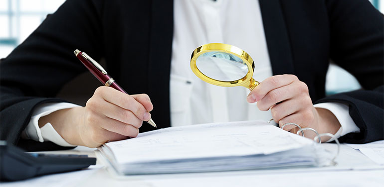 person looking through magnifying glass at documents