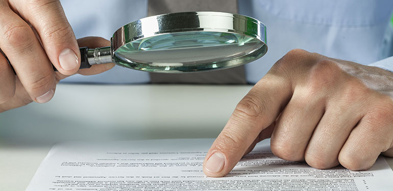 person reviewing document with a magnifying glass