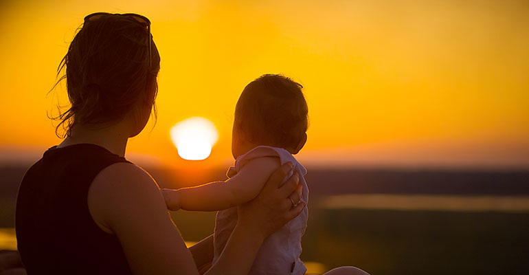 Women and son looking at a sunset