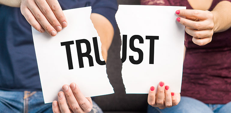 two people tearing piece of paper with the word trust on it