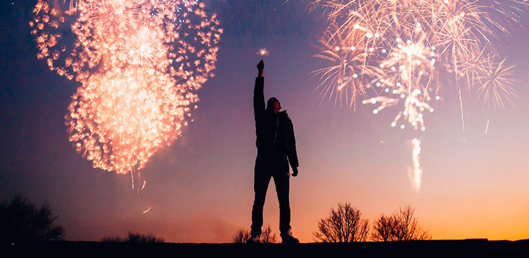Silhouette of man standing against a night sky full of fireworks