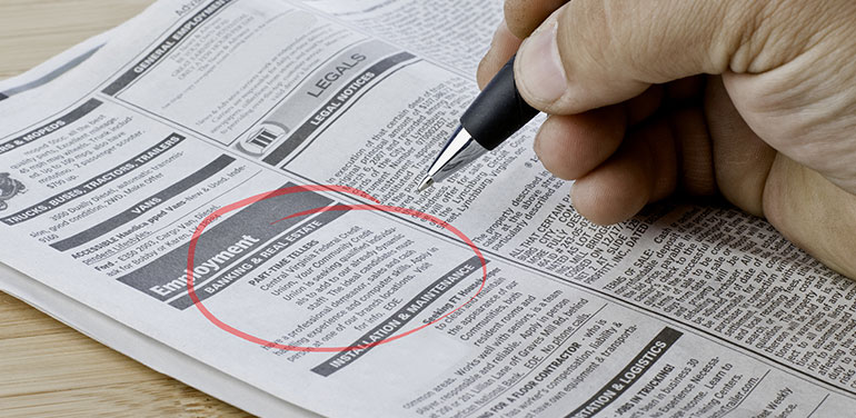 Close up of hand circling job in a newspaper