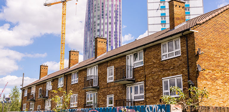 Row of houses with skyscrapers being built behind