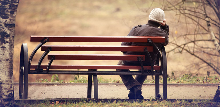 Lonely man sitting on a park bench