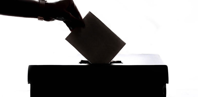 person putting a vote in box