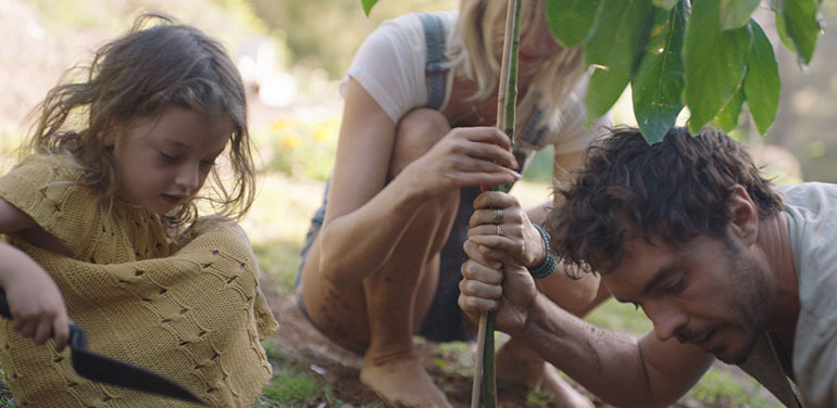 Still from the doco 2040 showing Gameau planting a tree with his wife and daughter.
