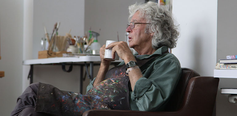 Michael Leunig drinking a cup of tea in his studio.