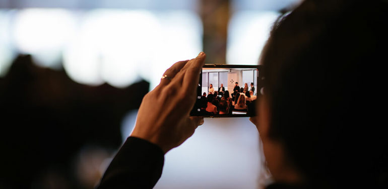 Image of someone taking a photo on their phone of a panel at the last Social innovation Summit