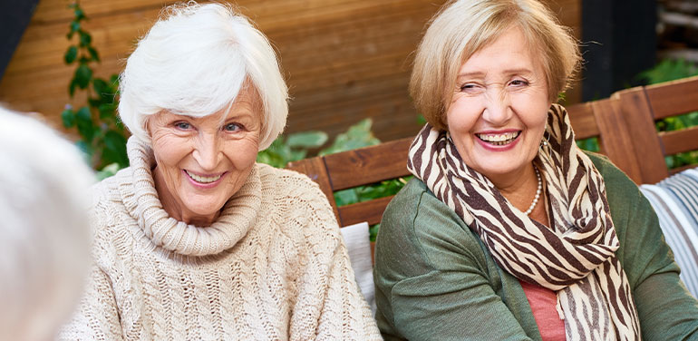 two older women talking and smiling in a group