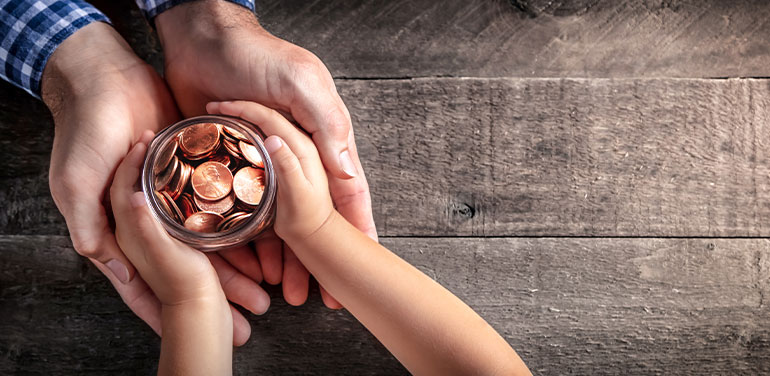 Mans hands holding childs hands with jar of coins
