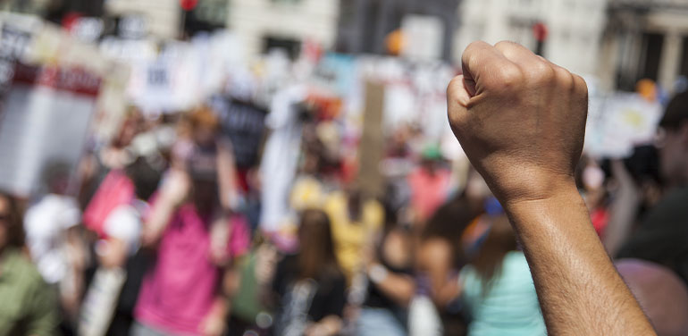 person raising fist in the air at a protest