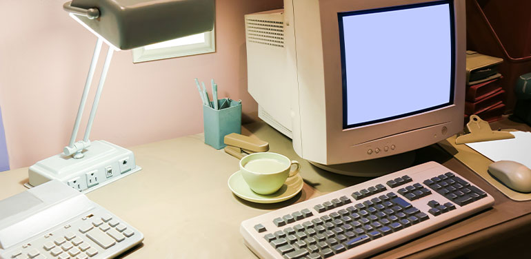 A desk from the 1990s with phone and PC