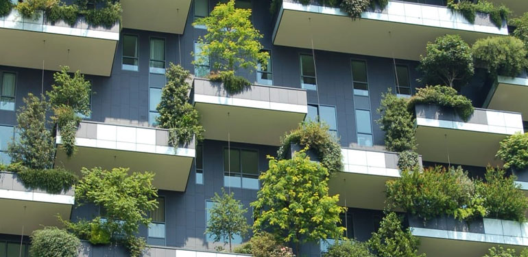 high rise with green trees planted on each balcony.