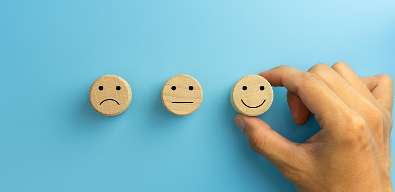 hand picking smile face icon on wooden cube on blue background.