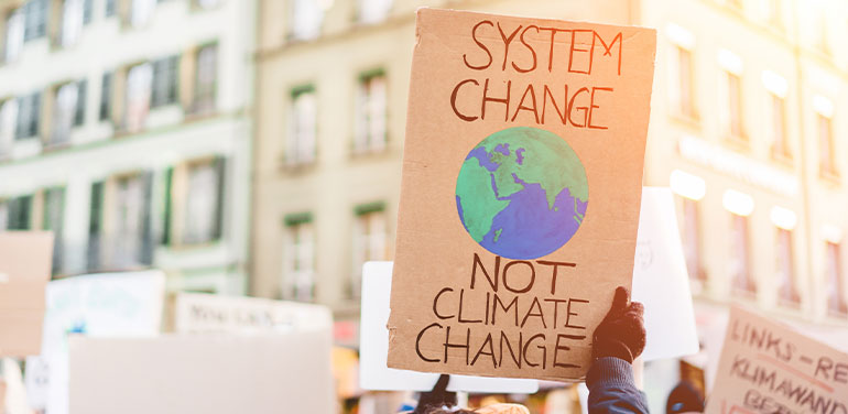 protest sign saying system change not climate change