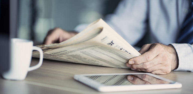 close up of man's hands holding a newspaper
