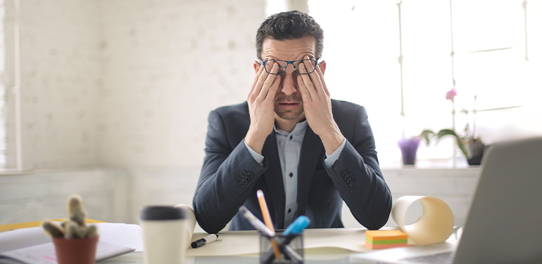 man looking stressed at desk
