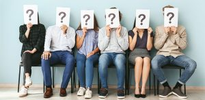 people hiding faces behind paper sheets with question marks while waiting for job interview