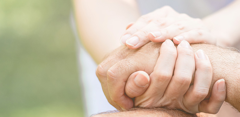 close up of carer holding patient's hands in her hands