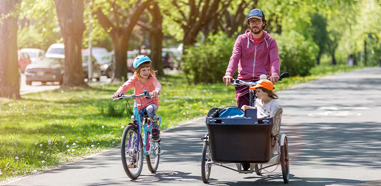 Father and daughters having a ride with cargo bike
