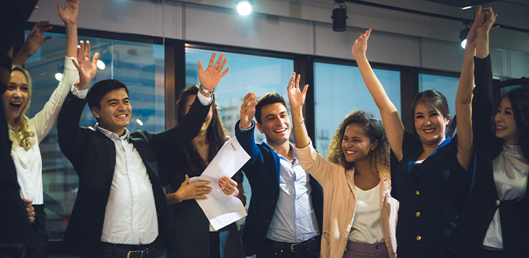 group of smiling business people with their hands in the air