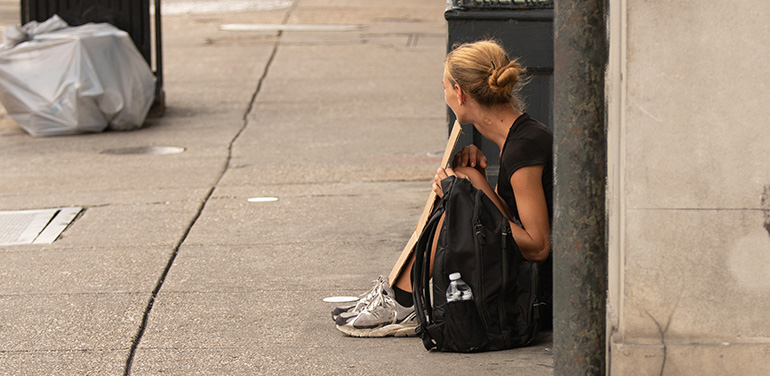 A homeless woman sitting on a street holding a cardboard sign