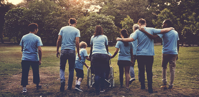 group of people including a person in a wheelchair all wearing blue tshirts and walking away from the camera