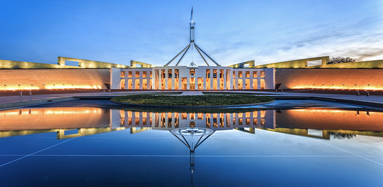 Parliament House in Canberra at night. Silhouette of building reflected in water.