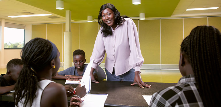 black woman standing at a desk teaching children