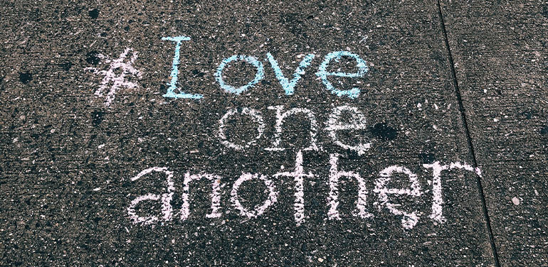 words Love one another written in chalk on the pavement